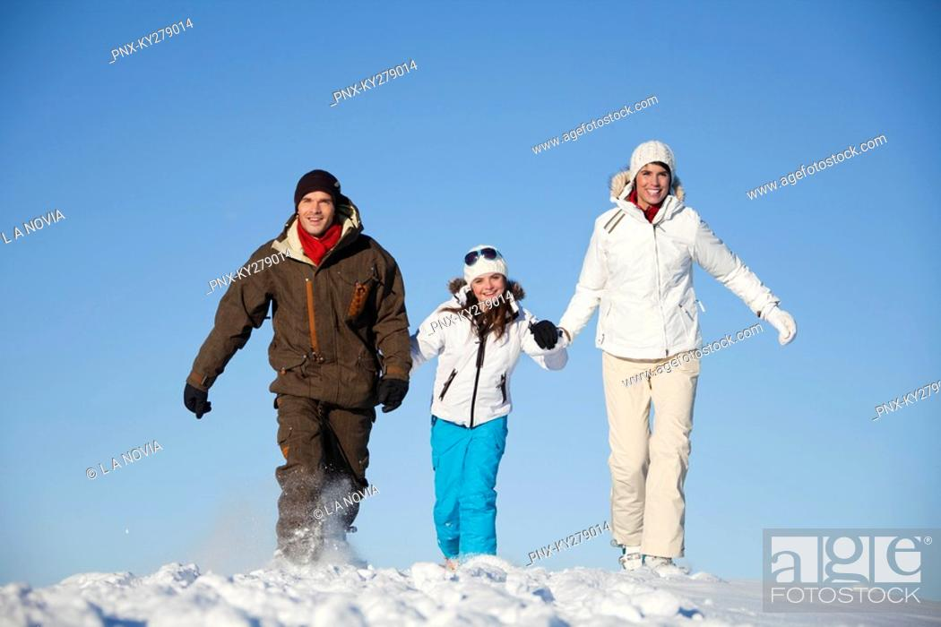 Stock Photo: Couple and daughter in ski wear walking in snow.