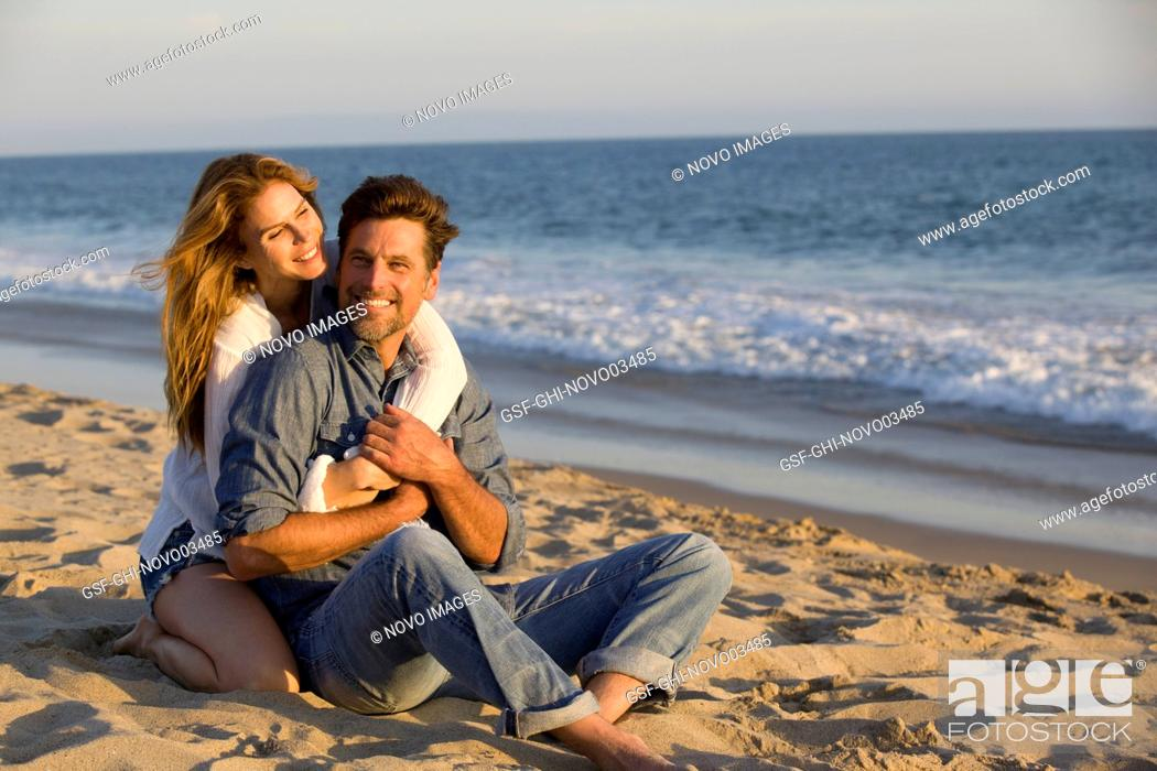 Imagen: Affectionate Mid-Adult Couple Sitting on Sandy Beach.