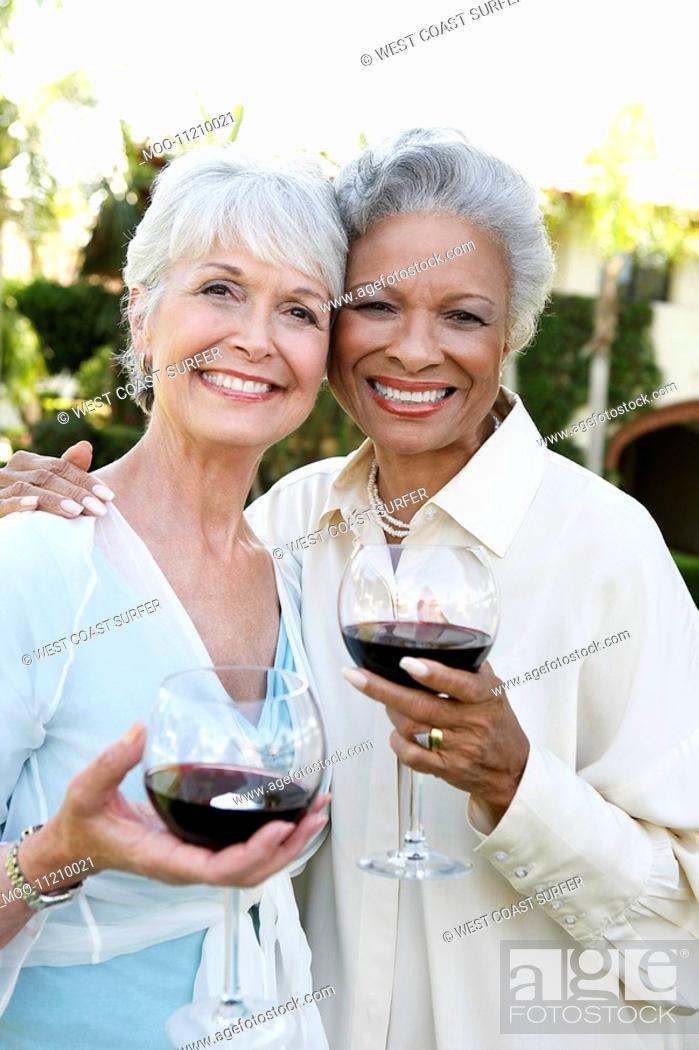 Stock Photo: Middle-aged Friends standing outside Drinking Wine from wineglasses.