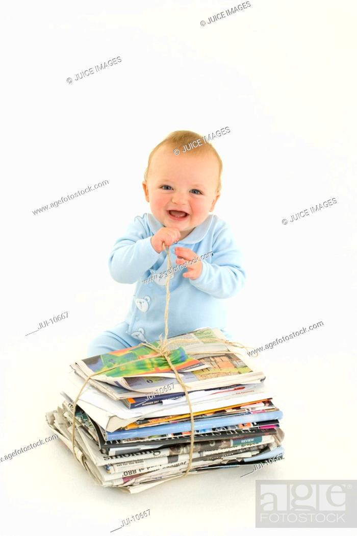 Stock Photo: Baby boy 3-6 months by bundle of newspapers, smiling, elevated view.
