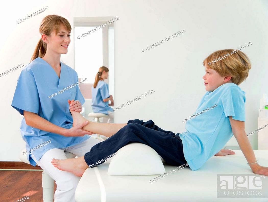 Stock Photo Doctor Examining Boys Feet In Office