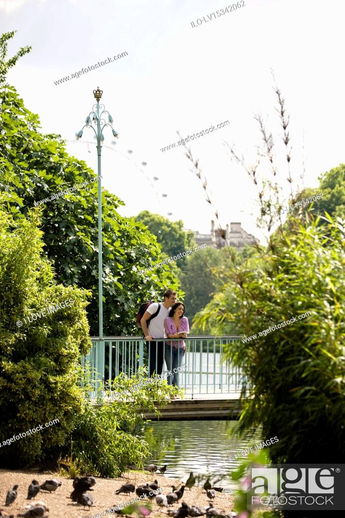 Stock Photo: A young couple standing on a bridge in St James Park.