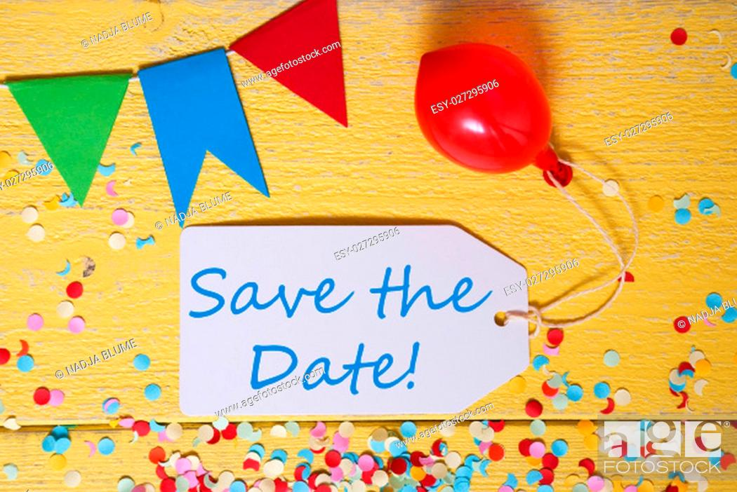 Stock Photo: White Label With English Text Save The Date. Party Decoration Like Streamer, Confetti And Balloon. Flat Lay Or Top View. Yellow Wooden Background.