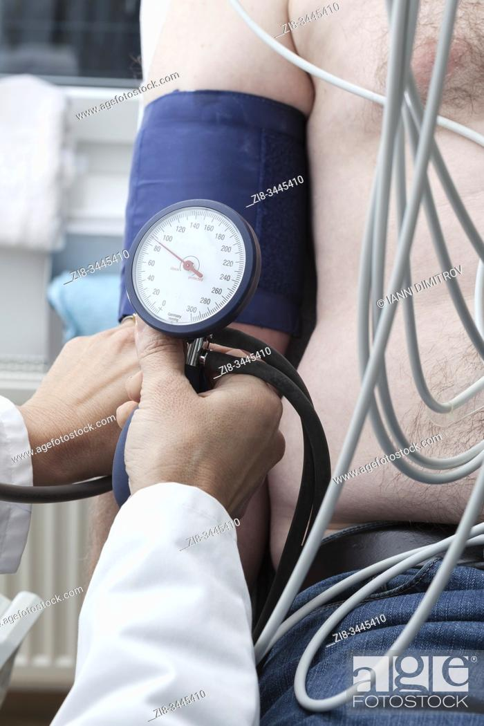 Stock Photo: Cardiollogist monitors blood pressure of patient during cardiology strees test.