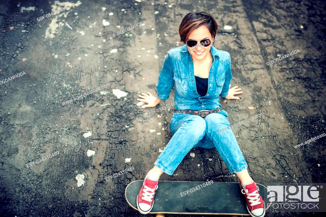 Stock Photo: Modern girl with skateboard and sunglasses posing and smiling while sitting on terrace. Hipster girl wearing sunglasses and playing with skateboard.
