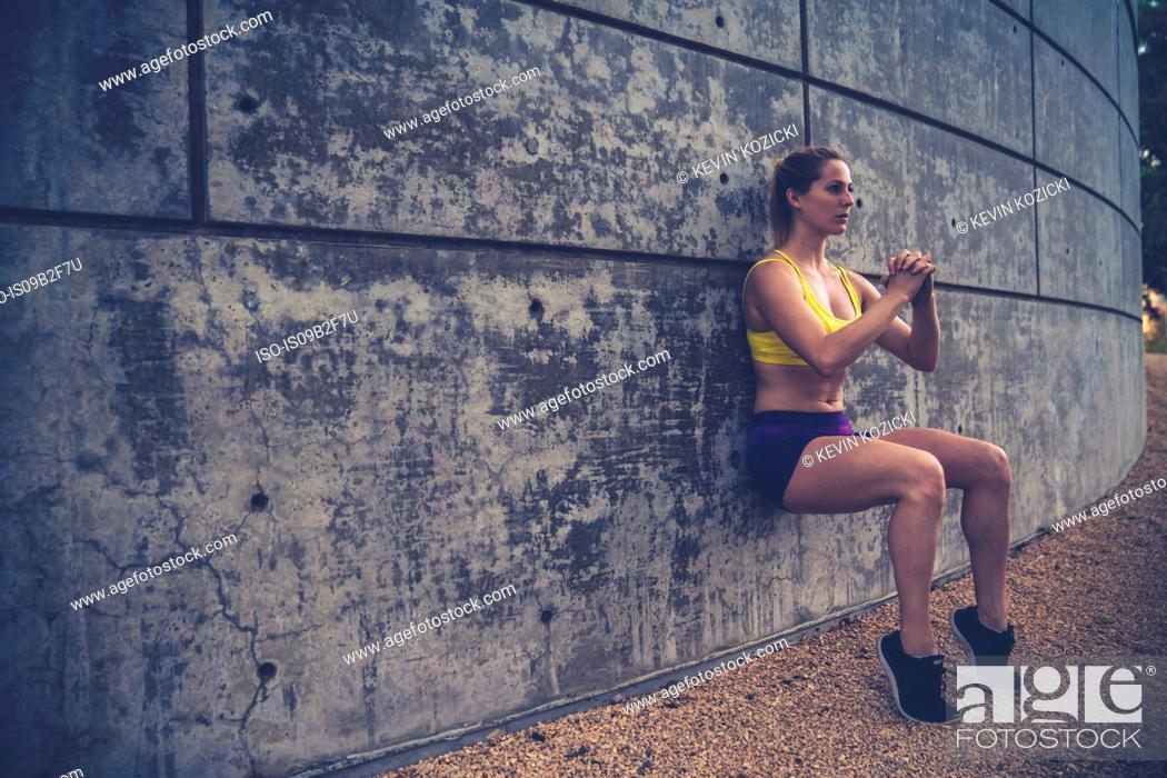 Stock Photo: Young woman leaning against wall outdoors, doing squats.