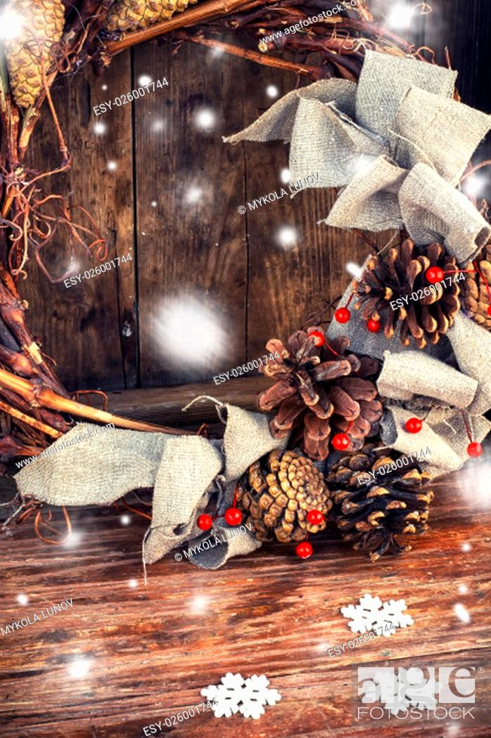 Stock Photo: Woven from twigs and decorated with pine cones Christmas wreath on snowy wooden background.