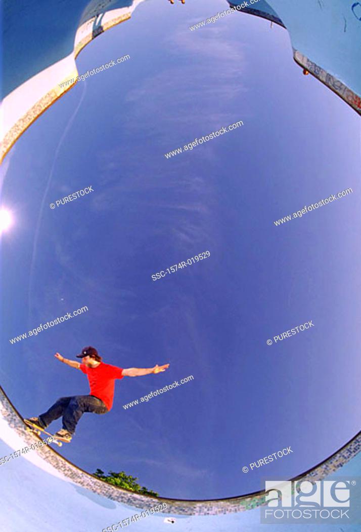 Stock Photo: Skateboarding in empty swimming pool (fish-eye lens).