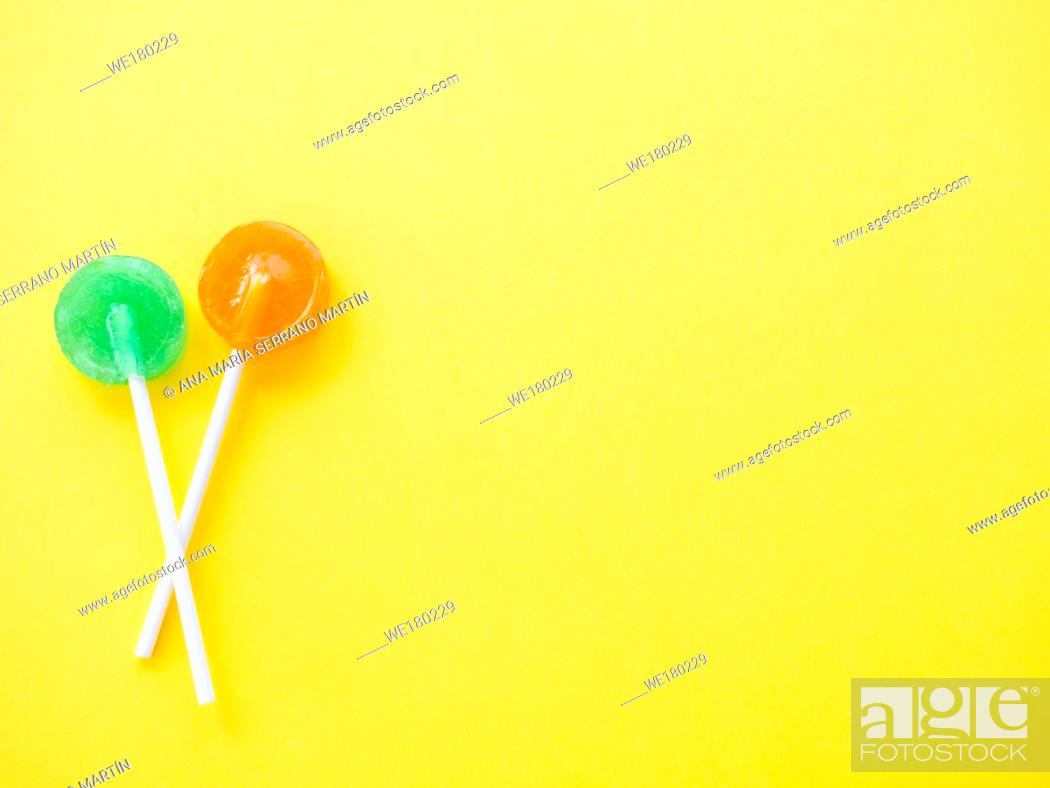 Stock Photo: Green and orange lollipops on a yellow background.