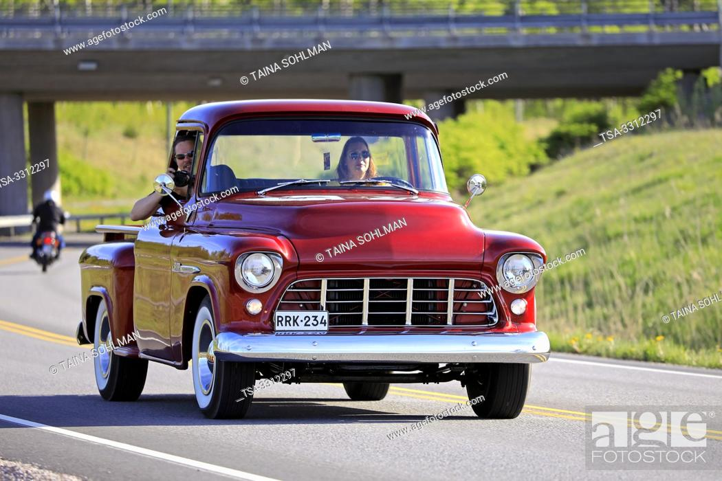 Stock Photo: Salo, Finland. May 18, 2019. Woman drives a mid-1950s Chevy pickup, the man on passengers seat is photographing on Salon Maisema Cruising 2019.