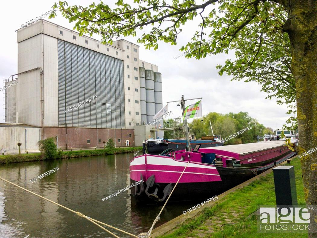 Photo de stock: Helmond, Netherlands. Agricultural animal food factory alongside a canal with moored barge.