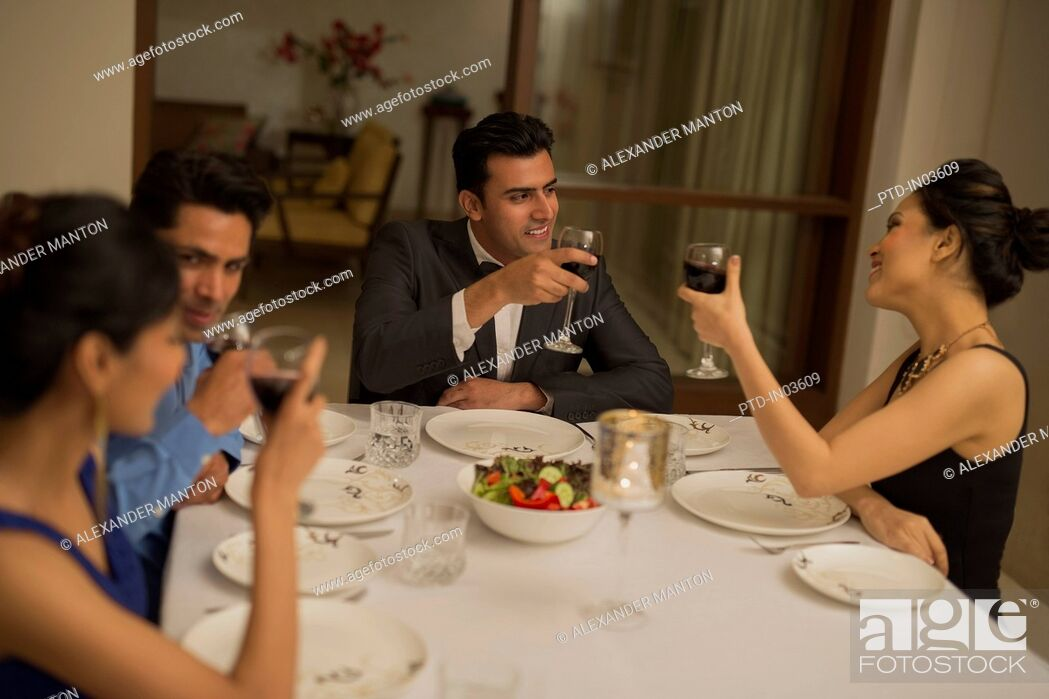 Imagen: Four friends at formal dining table.