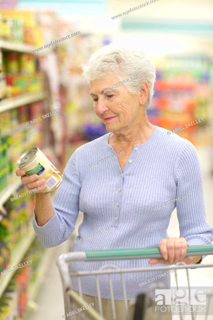 Stock Photo: Woman reading can label in store.