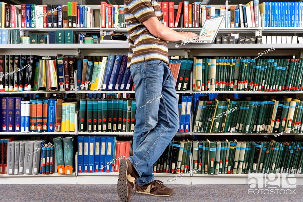 Stock Photo: Young man studying in library, side view low section.