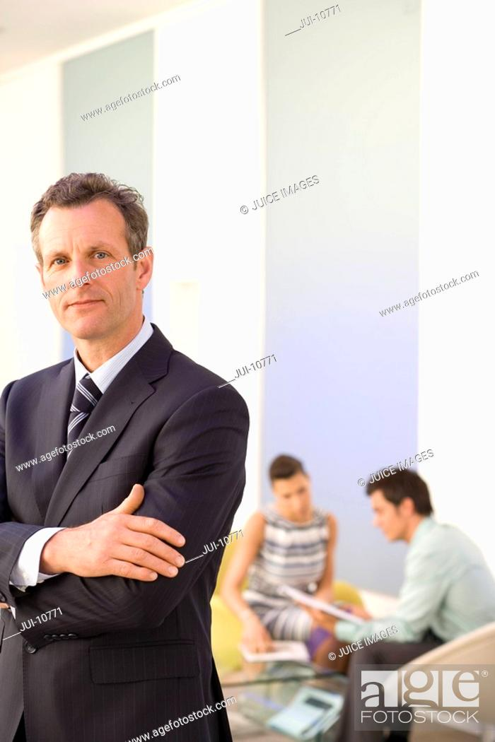 Stock Photo: Businessman with arms crossed in office by colleagues having meeting, portrait, close-up.