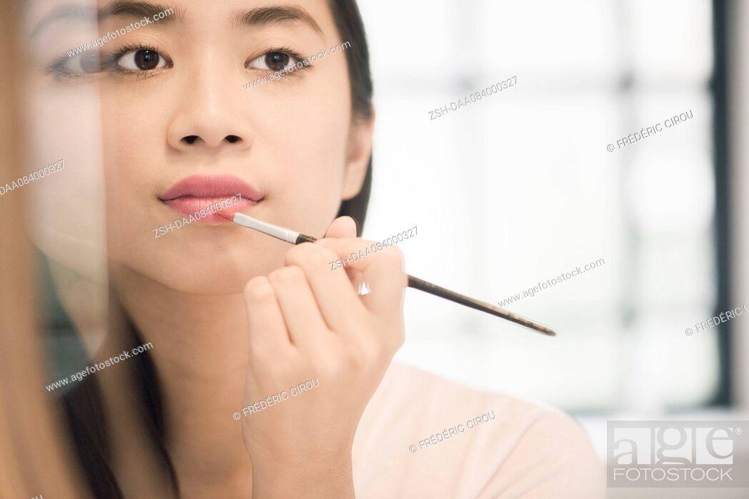 Stock Photo: Woman applying lipstick.