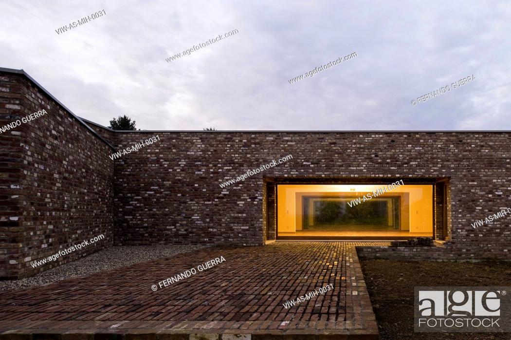 Stock Photo: MUSEUM INSEL HOMBROICH ALVARO SIZA RUDOLF FINSTERWALDER NEUSS 2008 DETAIL OF EXTERIOR FACADE WITH BRICK WALL, BRICK PAVEMENT AND ILLUMINATED COURTYARD WINDOW.