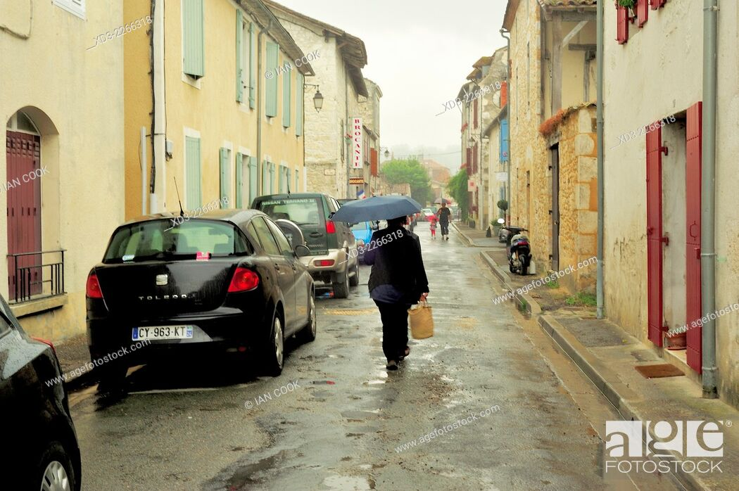 Stock Photo: woman with an umbrella, Eymet, Dordogne Department, Aquitaine, France.