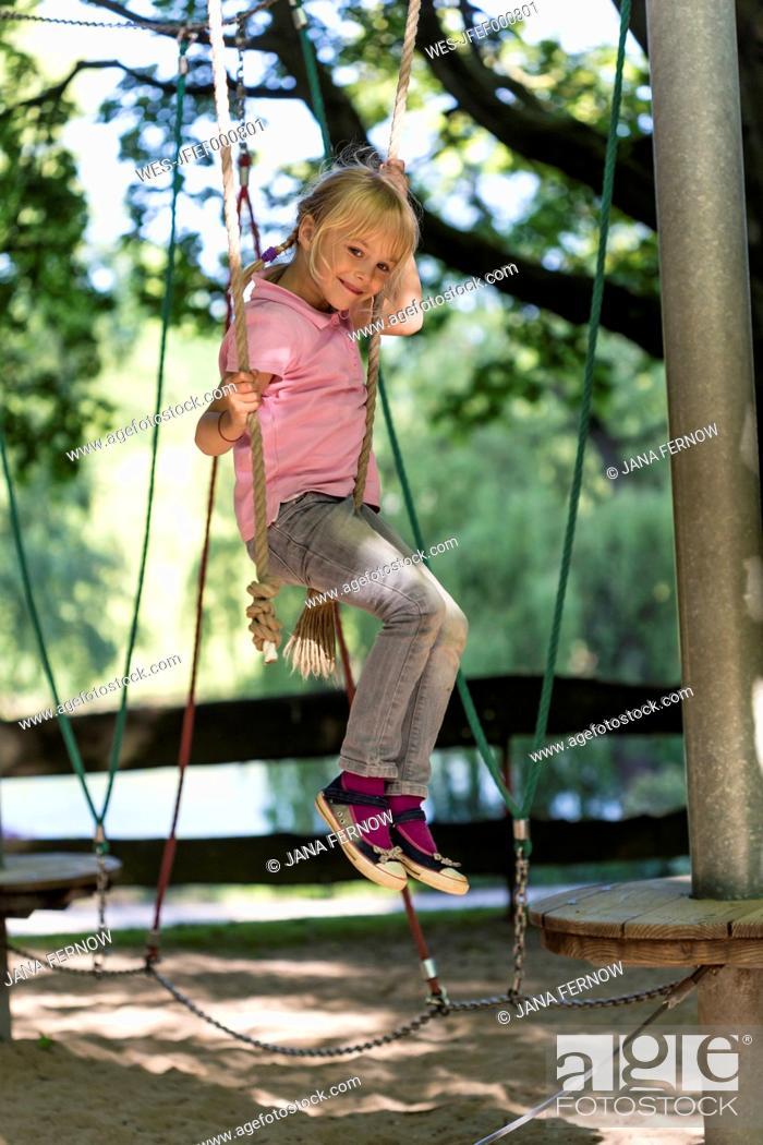 Stock Photo: Little girl climbing on a playground.