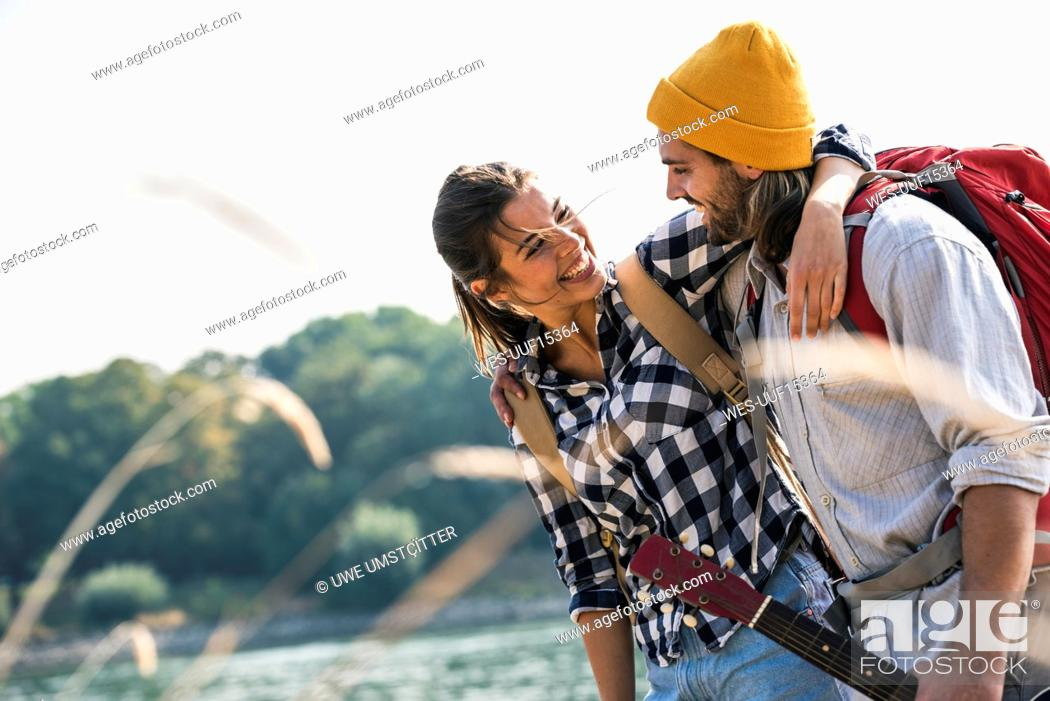 Imagen: Happy young couple with backpacks and guitar embracing at the riverside.
