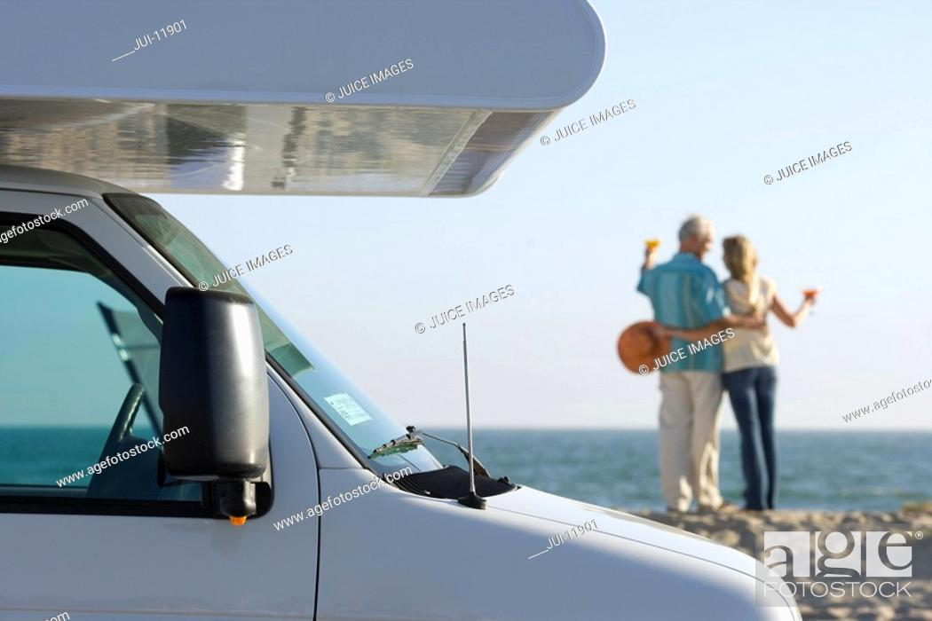 Stock Photo: Mature couple arm in arm with cocktails by motor home on beach, rear view.