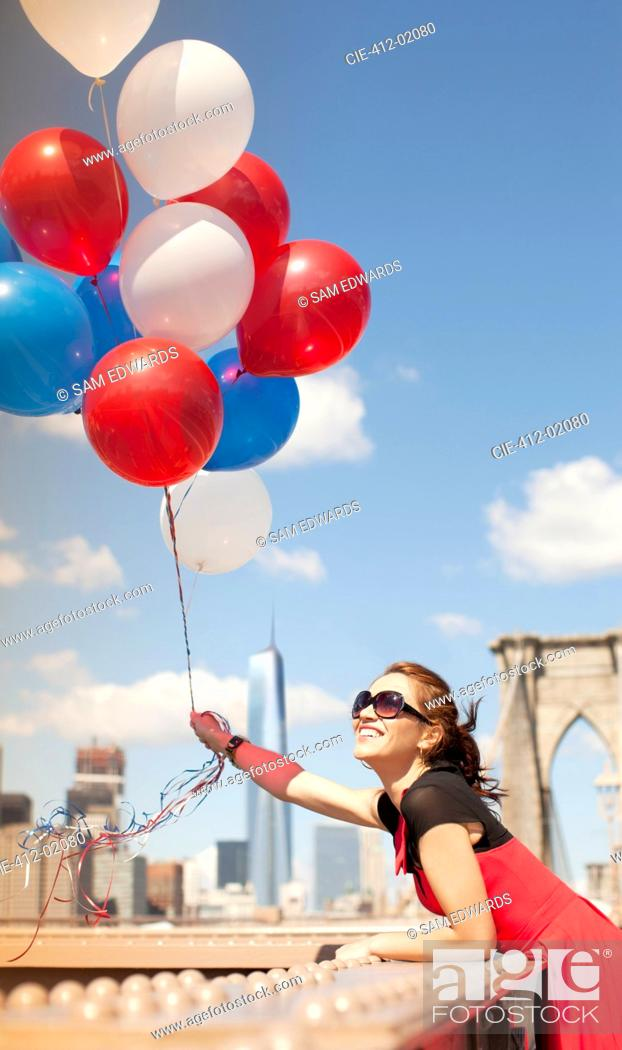 Stock Photo: Woman holding bunch of balloons on urban bridge.