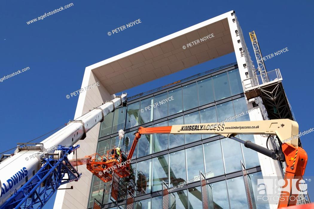 Stock Photo: construction workers working at height to install cladding on Southern Operational Command Unit Southampton.