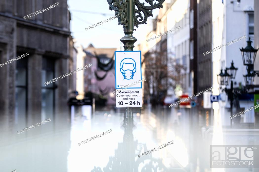 """Stock Photo: 04 November 2020, North Rhine-Westphalia, Duesseldorf: A sign with the bilingual information """"""""Mask duty - Cover your mouth and nose 10-24h"""""""" is attached to a."""