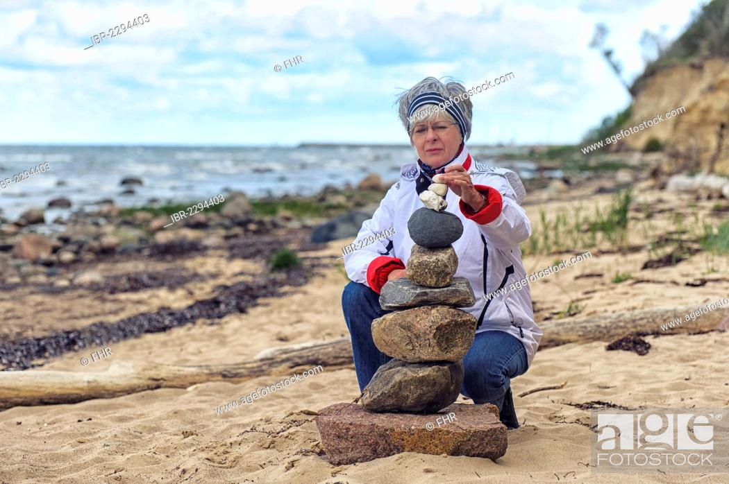 Imagen: Woman building a cairn on the beach, Timmendorf on the Island of Poel, Mecklenburg-Western Pomerania, Germany, Europe.