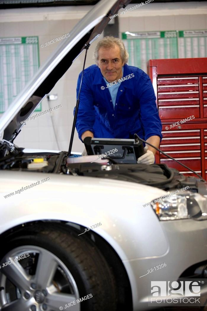 Stock Photo: Mechanic with diagnostic computer by open bonnet of car, portrait, low angle view.