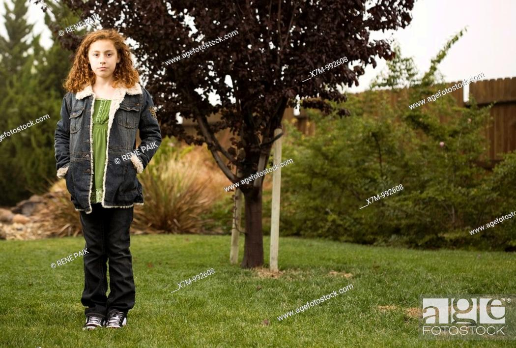 Stock Photo: A growing young mixed race mexican & caucasian girl standing in front of a young sapling.