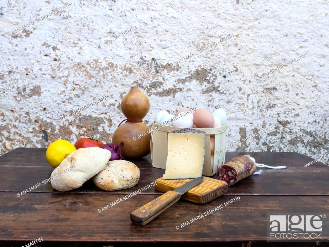 Imagen: Traditional spanish food on an old wooden table, Iberian pork sausages, bread, eggs, cheese and vegetables and an old knife.