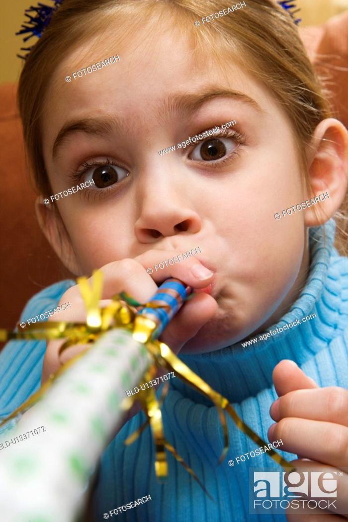 Stock Photo: Caucasian girl blowing noisemaker and making facial expression.