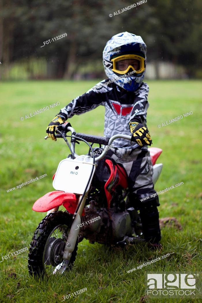 Photo de stock: A boy in protective sportswear sitting on a dirt bike.