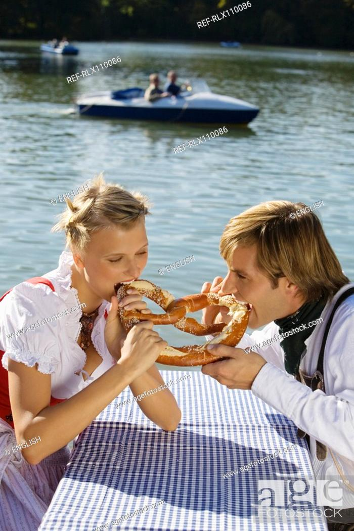 Stock Photo: Young couple in traditional Bavarian outfit, eating Pretzel, Munich.