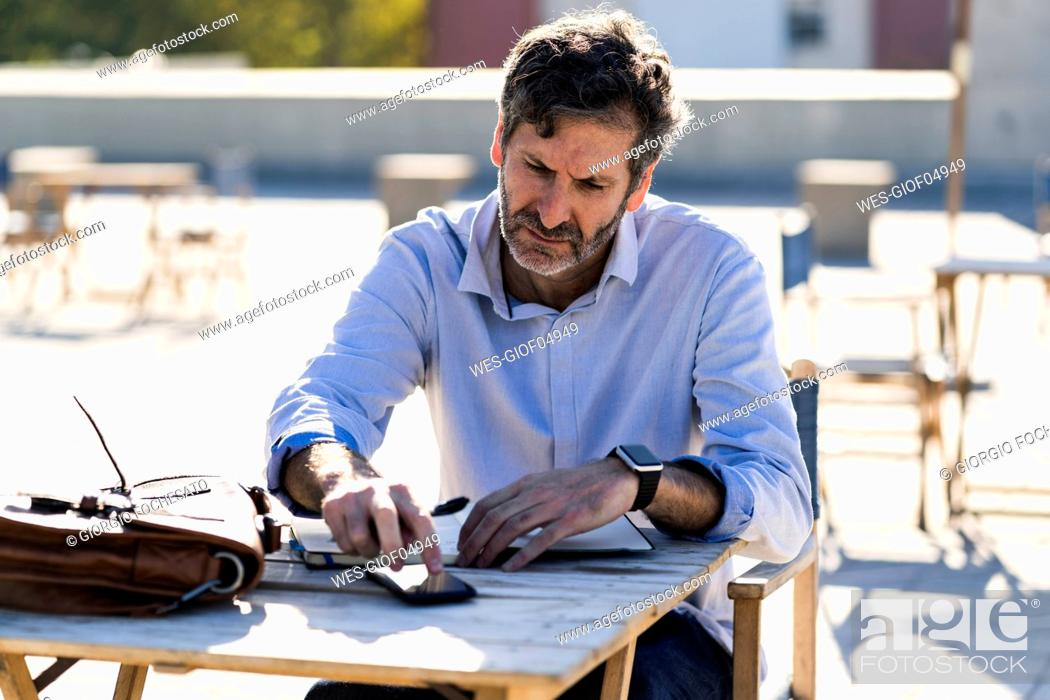 Stock Photo: Mature man sitting at outdoor table with cell phone and notebook.