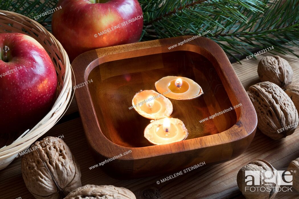 Stock Photo: Christmas decoration on a table - apples, pine branches, walnuts and floating candles made from nutshells and beeswax.