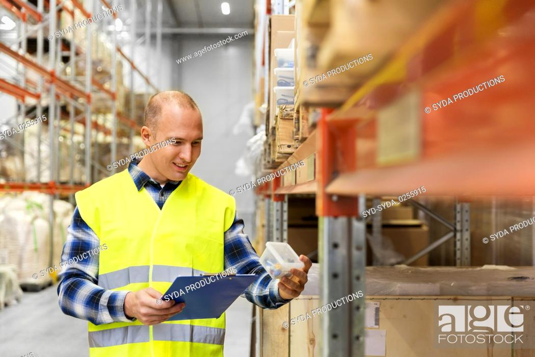 Stock Photo: warehouse worker with clipboard and plastic box.