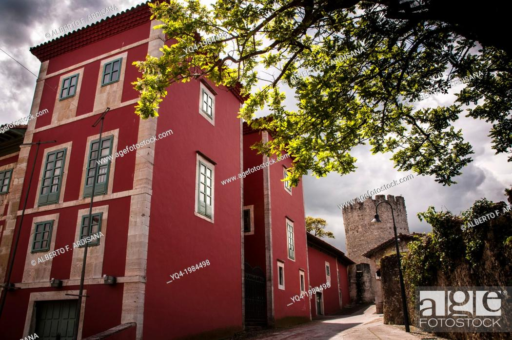 Stock Photo: The House of Culture, in the old town of Llanes. In the background, the tower of the wall .Llanes, Asturias, Spain.