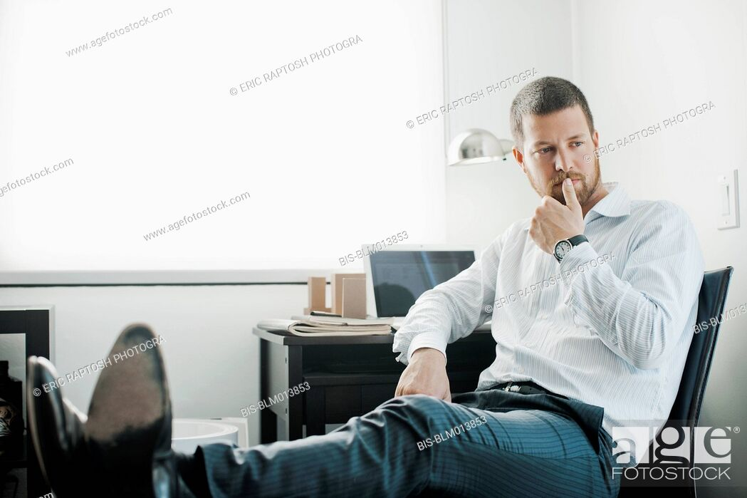 Imagen: Caucasian businessman sitting at desk with feet up.
