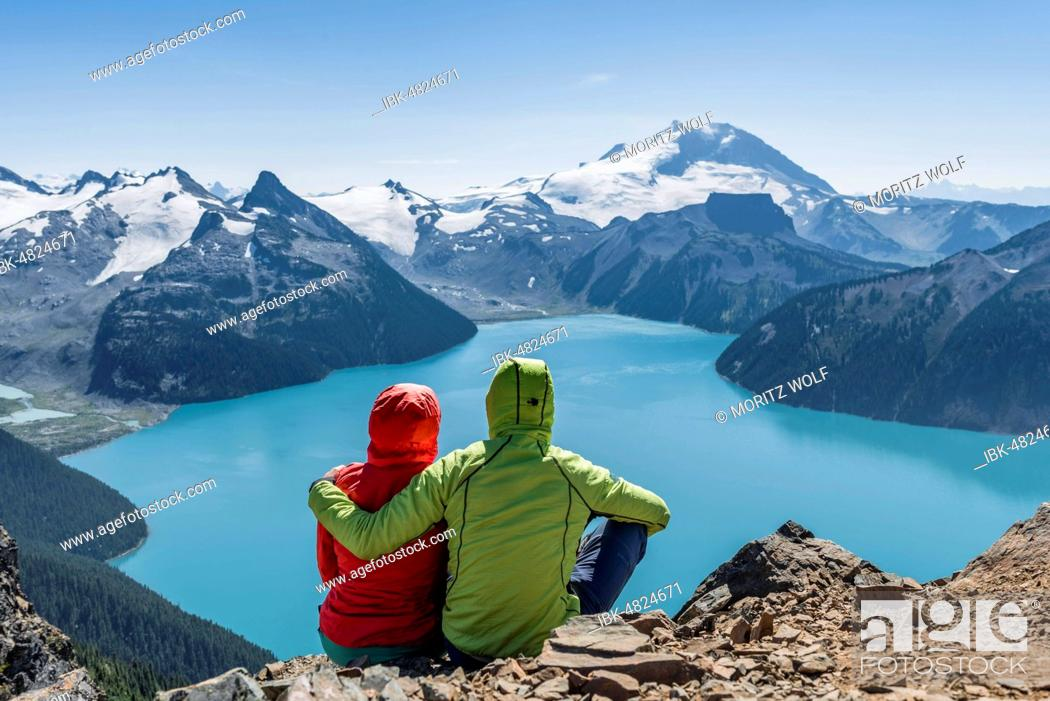 Stock Photo: View from Panorama Ridge trail, Two hikers sitting on a rock with Garibaldi Lake, turquoise glacial lake, Guard Mountain and Deception Peak, Glacier.