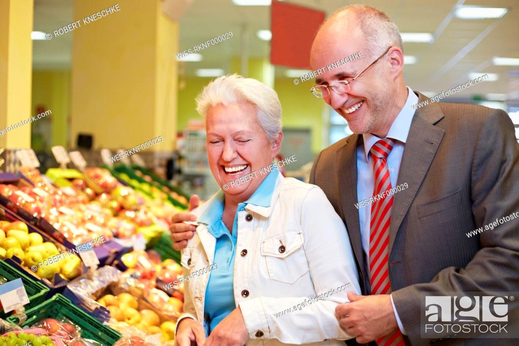 Stock Photo: Germany, Cologne, Mature couple in supermarket, smiling.