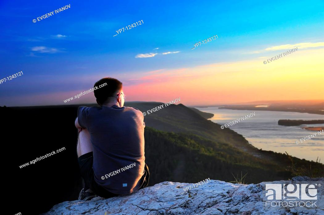 Stock Photo: Boy watches sunset skies in Russian National Park sitting on a steep rock of Zhiguli mountains.