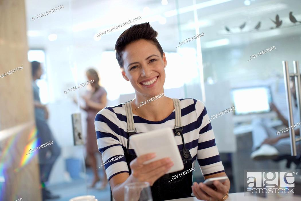 Stock Photo: Portrait smiling, confident creative businesswoman using digital tablet in office.