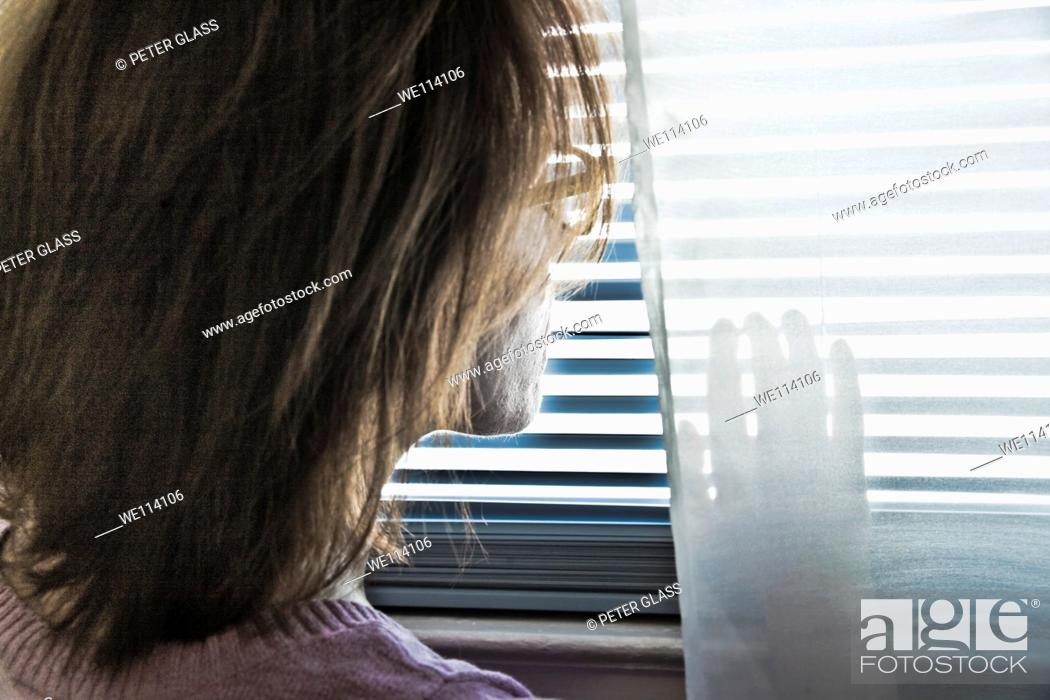 Stock Photo: Woman looking out her bedroom window.