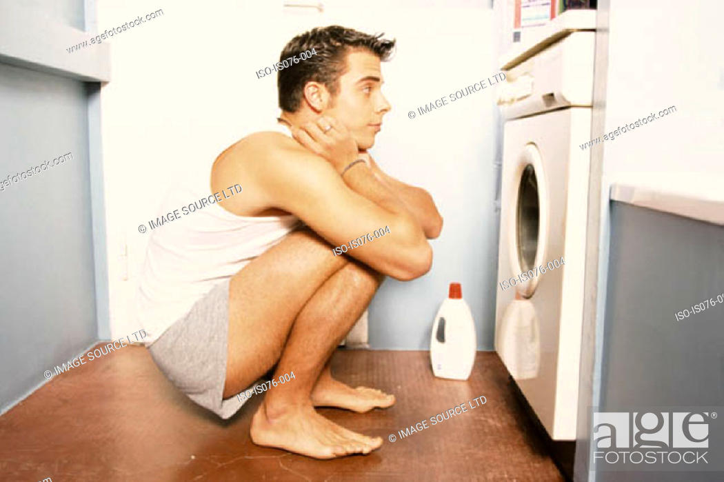 Stock Photo: Man watching washing machine.