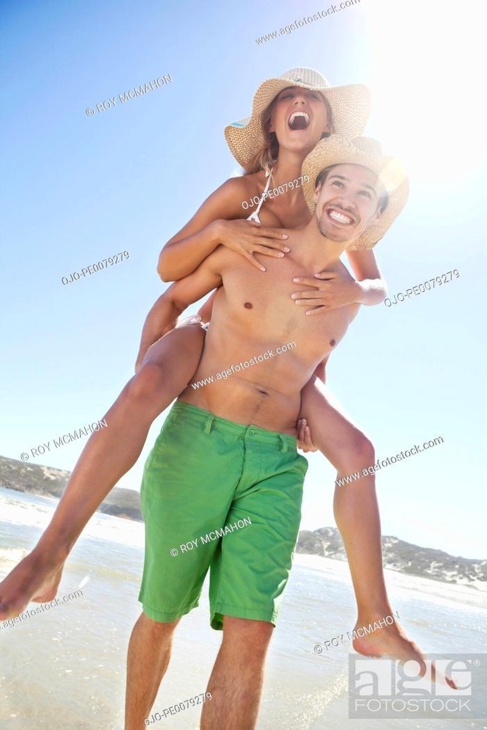 Stock Photo: Man giving girlfriend piggyback ride on beach.