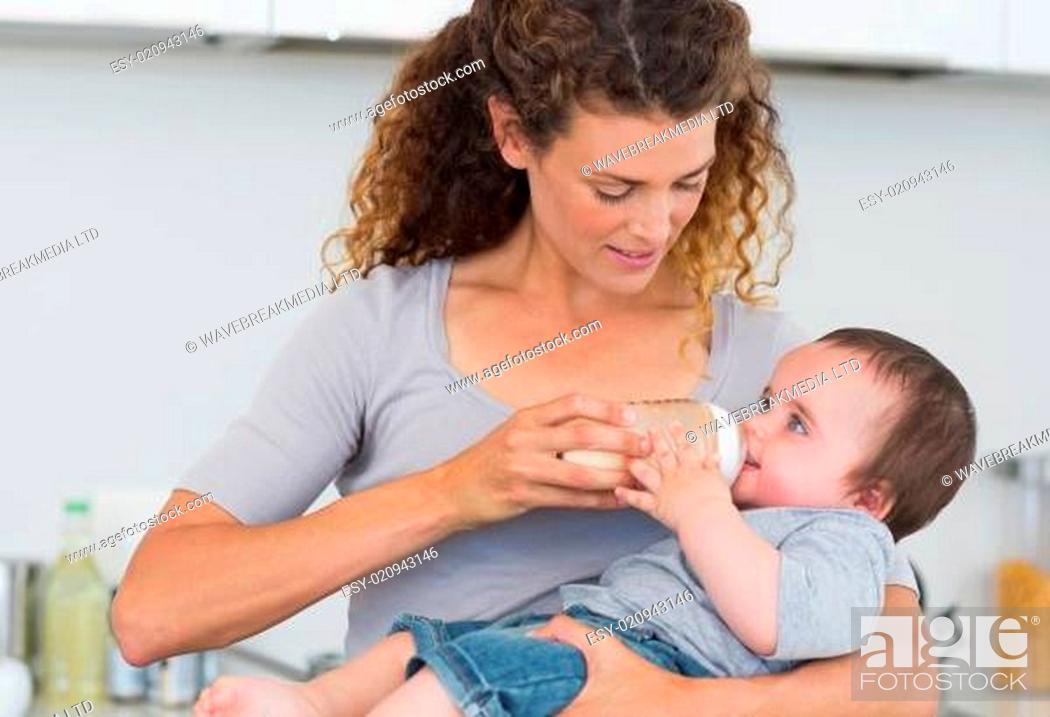 Stock Photo: Beautiful mother feeding milk to baby.