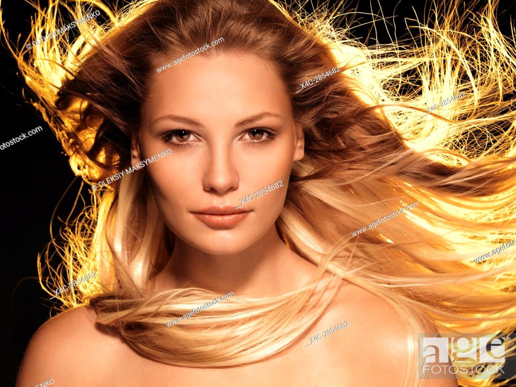 Stock Photo: Beauty face portrait of a woman with long glowing flying golden blond hair front view.