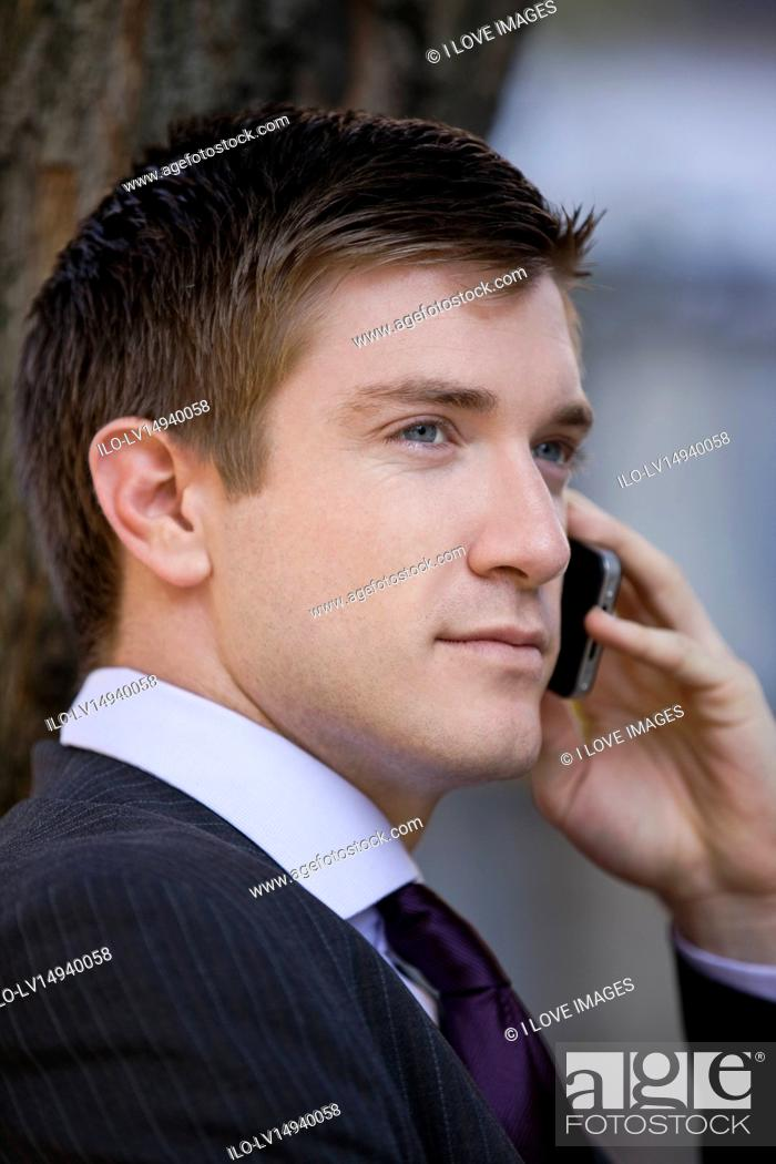 Stock Photo: Portrait of a businessman using his mobile phone, outside.